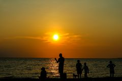 siluetee el juego de la gente con el perro en puesta del sol de la playa Fotos de archivo libres de regalías