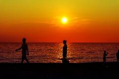 siluetee el juego de la gente con el perro en puesta del sol de la playa Fotos de archivo
