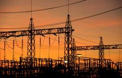 Siluetee el polo de poder de la fuente de alto voltaje en tiempo de la tarde Fotografía de archivo