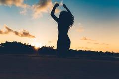 siluetee el retrato de la muchacha del verano que salta con las manos en aire en la arena blanca en la isla exótica en la puesta  Fotos de archivo