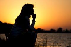 Siluetee el retrato de una mujer joven hermosa que se sienta en una silla por el río en el amanecer Imagen de archivo libre de regalías