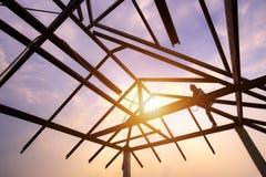 Siluetee el soldador en la estructura de tejado de acero, estructura del ro del acero Fotografía de archivo
