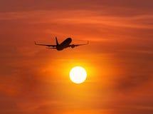 Siluetee el vuelo del aeroplano del pasajero sobre el sol durante puesta del sol foto de archivo