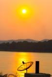 Siluetee la antena parabólica en la reflexión en el río en soles Imagen de archivo