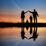 Siluetee la casa de la familia en puesta del sol