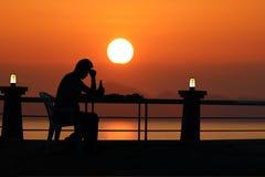 Siluetee la cerveza de consumición del hombre triste en la playa con el sunse rojo del cielo imagen de archivo libre de regalías