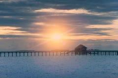 Siluetee la choza sobre la agua de mar reservada transparente en una puesta del sol, entonando maldives imagen de archivo