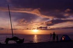Siluetee a la familia que acampa en la playa con el velero Imagen de archivo