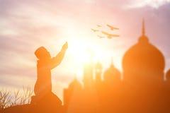 Siluetee la fe de rogación del muchacho musulmán en dios de Alá del suprem del Islam imagenes de archivo