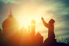 Siluetee la fe de rogación del muchacho musulmán en dios de Alá del suprem del Islam imagen de archivo