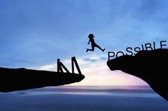 siluetee a la gente que salta sobre la palabra del frome de la roca imposible en el mar por la mañana Foto de archivo libre de regalías