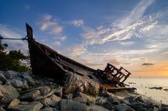 Siluetee la imagen del abandono naufragada en línea de la playa rocosa nube oscura y suavemente en el agua Fotografía de archivo libre de regalías