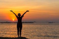 Siluetee la música que escucha del corredor de las mujeres y la libertad de sensación, feliz y disfrutando de puesta del sol de l foto de archivo libre de regalías