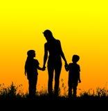 Siluetee la madre y al niño que llevan a cabo las manos en la puesta del sol Foto de archivo libre de regalías