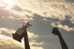 Siluetee la mano que sostiene la taza del trofeo del ganador en un campeonato fotografía de archivo libre de regalías