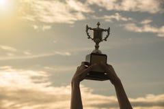 Siluetee la mano que sostiene la taza del trofeo del ganador en un campeonato fotografía de archivo
