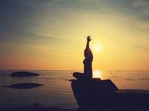 Siluetee a la muchacha de la yoga por la playa en la salida del sol que hace la meditación Imagen de archivo libre de regalías