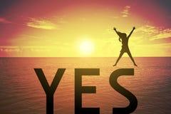 Siluetee a la mujer joven que salta y que aumenta para arriba su mano sobre concepto feliz en el texto del SÍ sobre una puesta de Fotografía de archivo