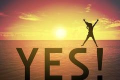 Siluetee a la mujer joven que salta y que aumenta para arriba su mano sobre concepto feliz en el texto del SÍ sobre una puesta de Fotos de archivo