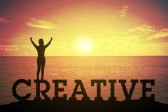 Siluetee a la mujer joven que se levanta y que aumenta su mano sobre concepto del ganador en el texto CREATIVO Foto de archivo libre de regalías