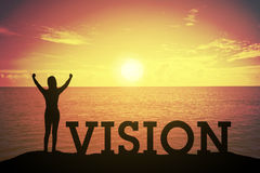Siluetee a la mujer joven que se levanta y que aumenta su mano sobre concepto del ganador en el texto de VISION fotografía de archivo