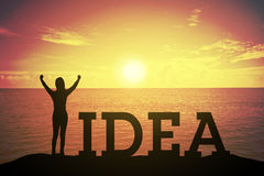 Siluetee a la mujer joven que se levanta y que aumenta su mano sobre concepto del ganador en el texto del IDEA Foto de archivo libre de regalías