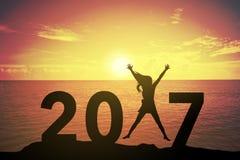 Siluetee a la mujer joven que se levanta y que aumenta su mano sobre concepto feliz encendido en 2017 sobre una puesta del sol o  Fotos de archivo libres de regalías