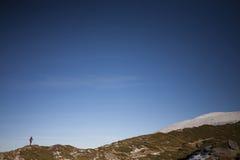 Siluetee a la mujer que corre a lo largo del canto de la montaña Imagen de archivo libre de regalías