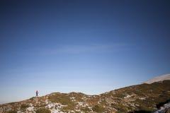 Siluetee a la mujer que corre a lo largo del canto de la montaña Fotos de archivo