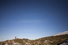 Siluetee a la mujer que corre a lo largo del canto de la montaña Imagen de archivo