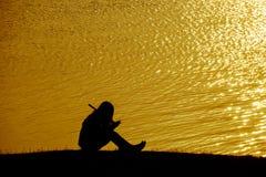 Siluetee a la mujer sola que se sienta en el campo de hierba cerca del agua en Fotos de archivo