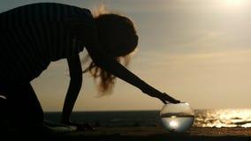 Siluetee a la niña que juega con sus pescados del oro del animal doméstico en costa del acuario en la puesta del sol almacen de video