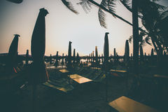 Siluetee la puesta del sol de la silla de playa en la playa Foto de archivo libre de regalías