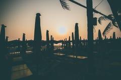 Siluetee la puesta del sol de la silla de playa en la playa Fotografía de archivo