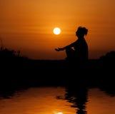 Siluetee la sentada de la mujer y la relajación contra puesta del sol anaranjada Imágenes de archivo libres de regalías
