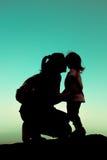 Siluetee la vista lateral de una madre joven que besa cariñosamente su litt fotografía de archivo