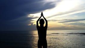 Siluetee la yoga de las prácticas de la mujer en el mar en la salida del sol