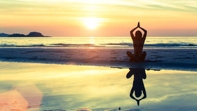 Siluetee la yoga practicante de la mujer en la playa en la puesta del sol Imágenes de archivo libres de regalías