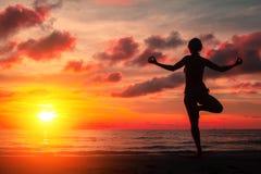Siluetee la yoga practicante de la mujer joven en la playa en la puesta del sol roja sangrienta surrealista Naturaleza Imagenes de archivo