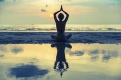 Siluetee la yoga practicante de la mujer joven en la playa en la puesta del sol surrealista Fotos de archivo
