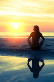 Siluetee la yoga practicante de la mujer sana joven en la playa Fotografía de archivo