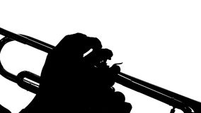 Siluetee las manos de hombres juegan en la trompeta de los botones cierre metrajes