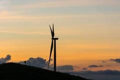 Siluetee las turbinas de los generadores de viento en el paisaje i del verano de la puesta del sol Imagen de archivo libre de regalías