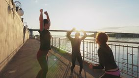 Siluetee a los atletas del salto contra el cielo con la puesta del sol, cámara lenta almacen de video