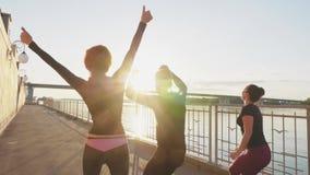 Siluetee a los atletas del salto contra el cielo con la puesta del sol, cámara lenta metrajes