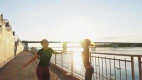 Siluetee a los atletas del salto contra el cielo con la puesta del sol, cámara lenta almacen de metraje de vídeo