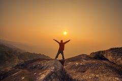 Siluetee los brazos del hombre aumentados en el cielo de la puesta del sol Imágenes de archivo libres de regalías