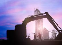 Siluetee los cargadores y al trabajador de construcción en un solar ov Fotos de archivo