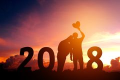 Siluetee los pares jovenes felices por 2018 Años Nuevos Foto de archivo