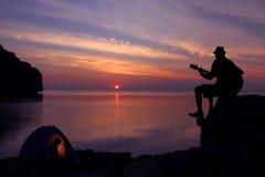 Siluetee los pares que acampan y que tocan una guitarra en la playa Imágenes de archivo libres de regalías